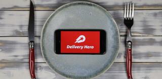 Delivery Hero App auf Smartphone auf Teller