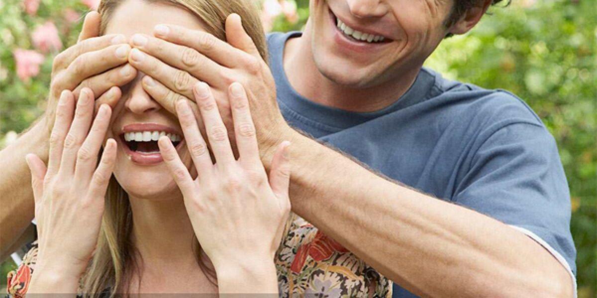 Mann hält Frau die Augen zu