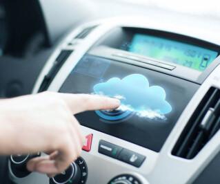 Hand drückt auf Display im Auto