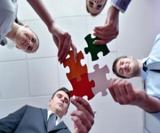 Vier Menschen halten Puzzleteil in der Hand