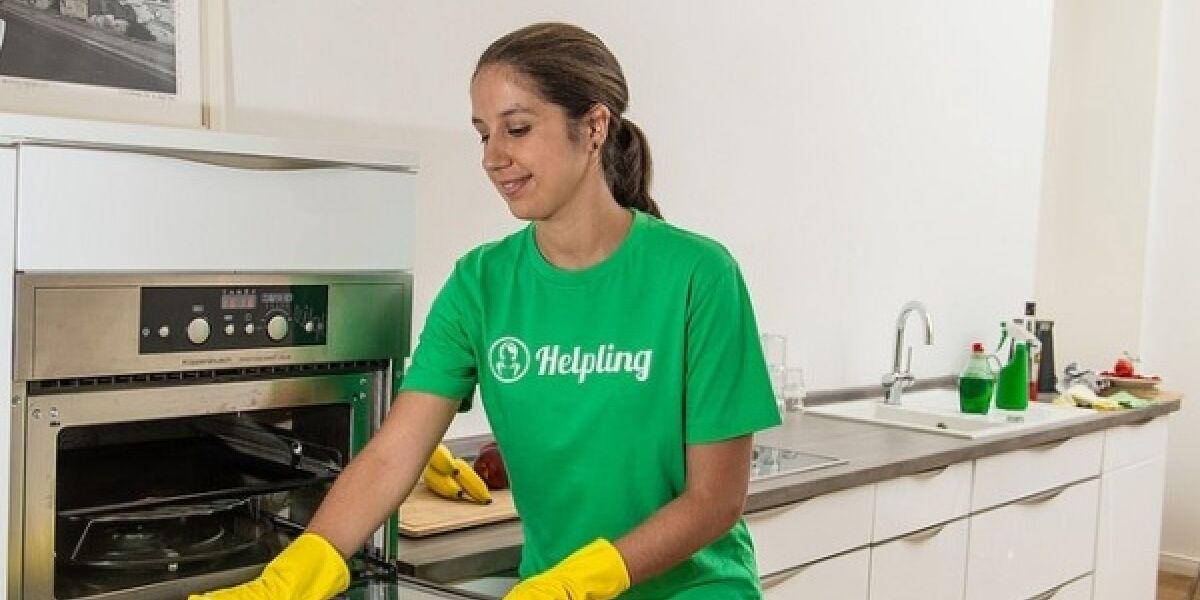 Frau putz mit gelben Handschuhen einen Ofen