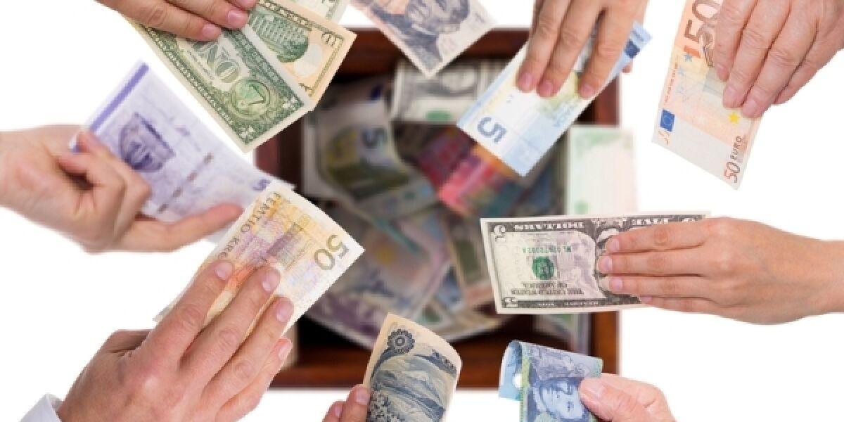 Geldscheine verschiedener Nationen werden in die Höhe gehalten