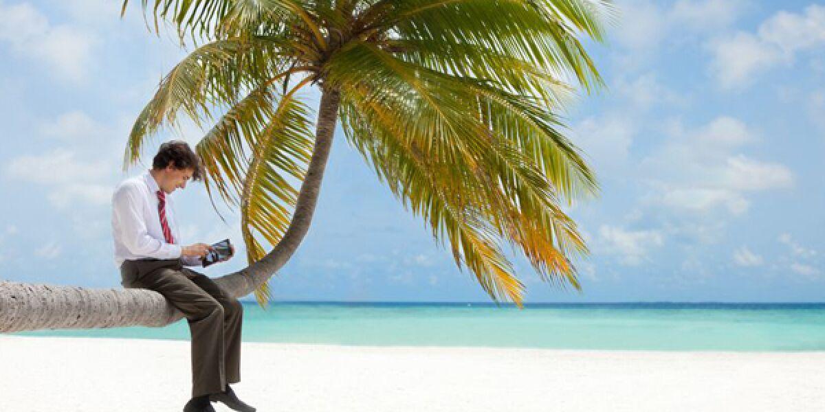 Mann in Krawatte sitzt mit Tablet auf einer Palme am Strand