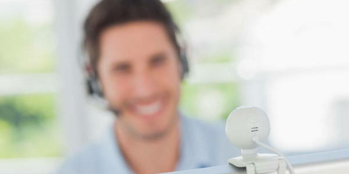 Mann mit Headset vor PC mit Webcam