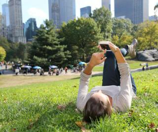 Smartphone-Nutzerin im Park
