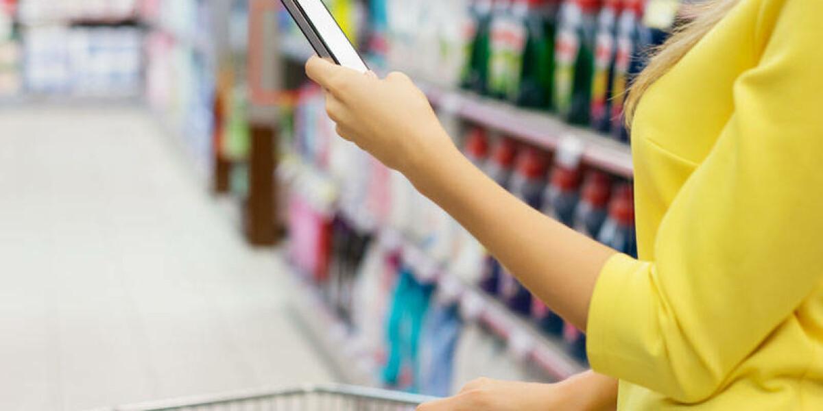 Frau im Supermarkt mit Smartphone