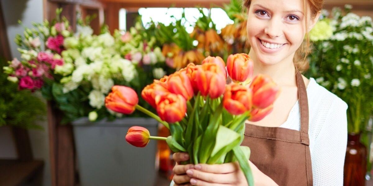 Blumen-Verkäuferin mit einem Strauß Tulpen