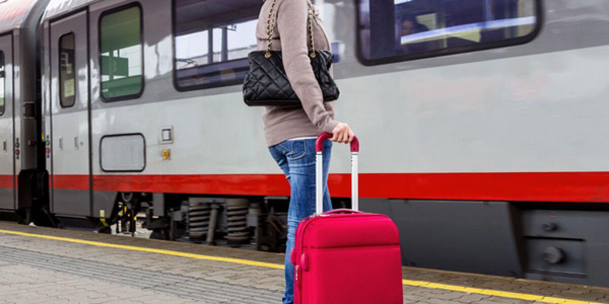 Frau vor Zug mit Koffer
