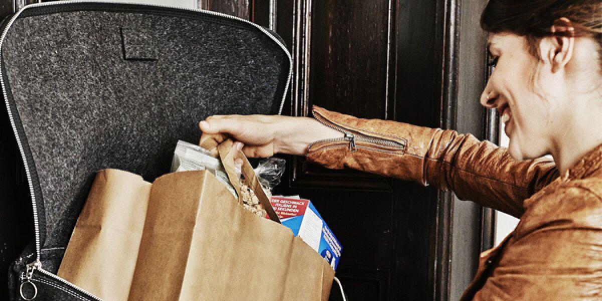 Frau nimmt aus einem Paketkasten an der Haustür ein Paket