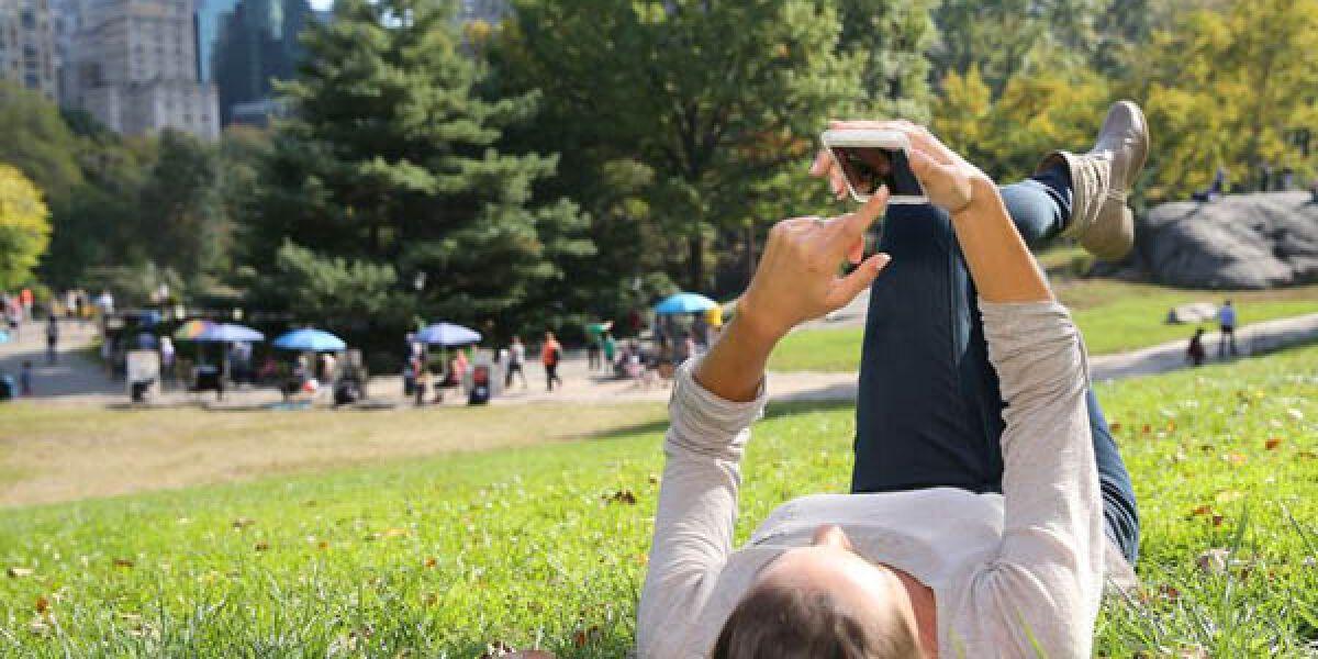 Frau liegt mit Smartphone im Park