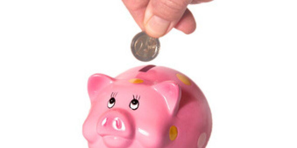 Eine Hand wirft eine Münze in ein rosa Sparschwein