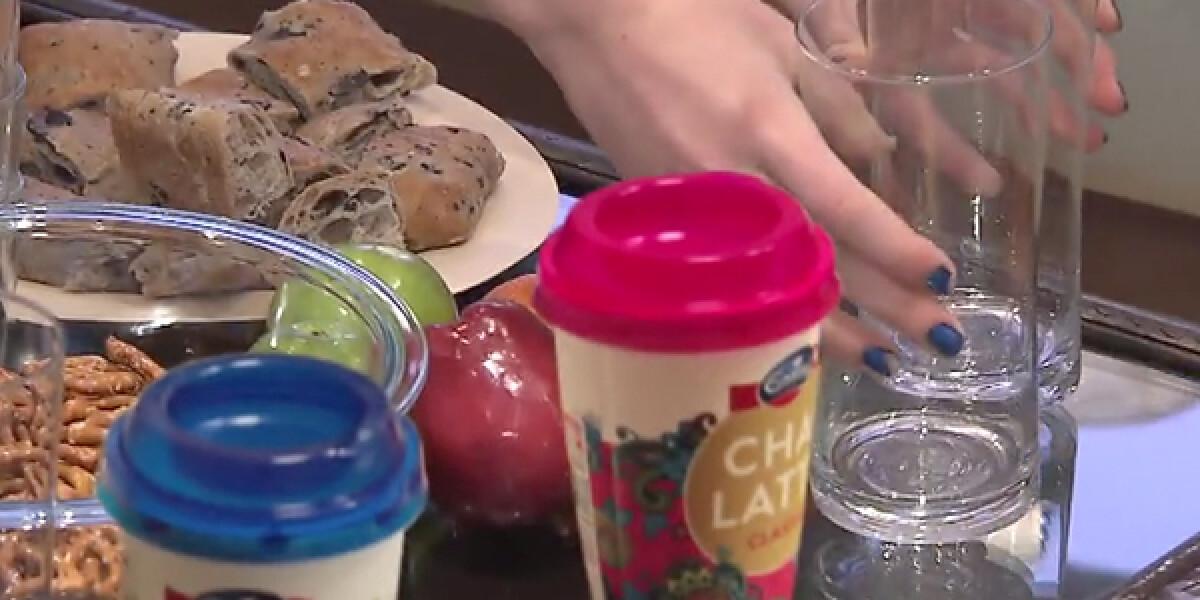 Tisch mit Gläsern und Tellern gefüllt, darauf Chai-Latte-Becher von Emmi