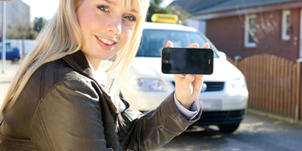 Frau mit Smartphone vor Taxi