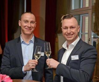 Zwei Männer stoßen mit einem Glas Sekt an