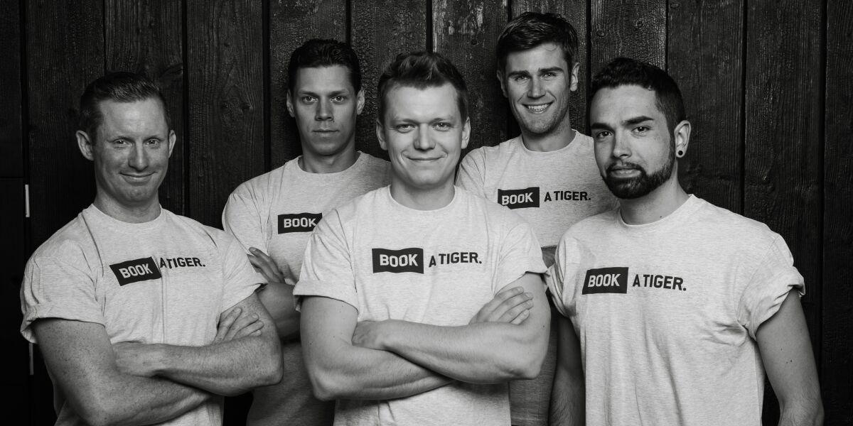 Fünf Männer von book a tiger blicken mit verschränken Armen in die Kamera