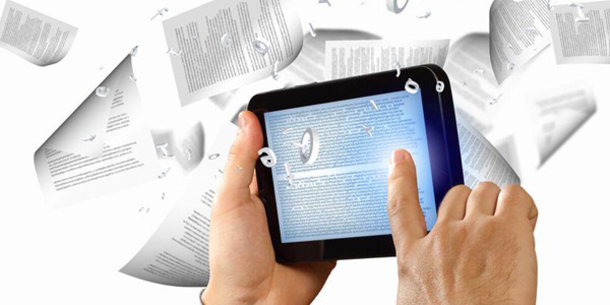 E-Book in der Hand und fliegende Blätter