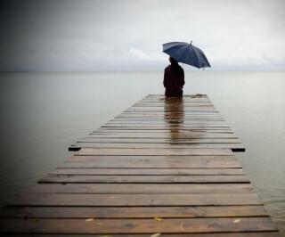 Frau mit Regenschirm allein auf Steg im Wasser