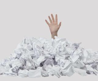Hand in Haufen zerknülltem Papier