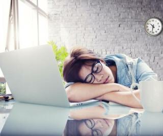 Schlafende Frau vor Rechner