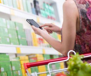 Frau nutzt Smartphone beim Einkauf