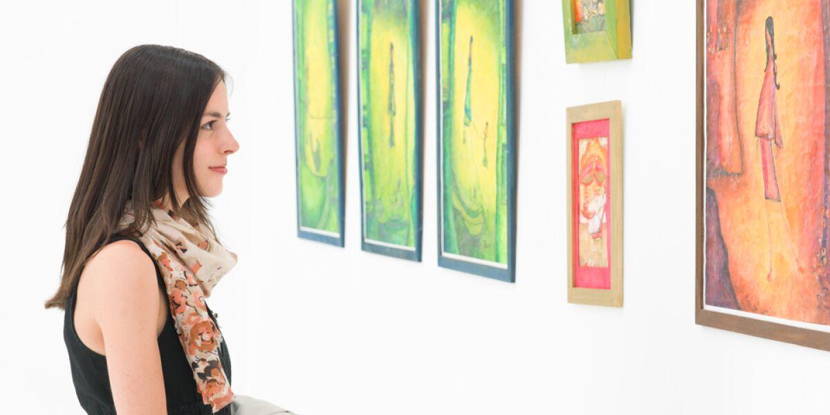 Frau sieht sich Bilder in einer Galerie an