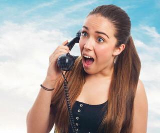 Überreaschte junge Frau am Telefon