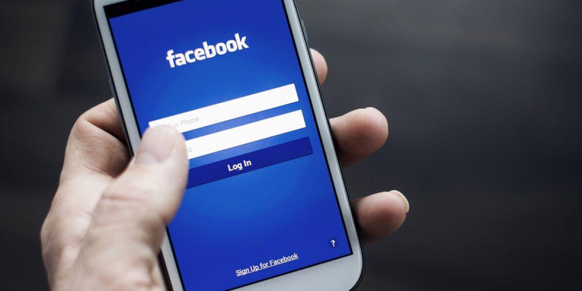 Hand hält Smartphone mit der Facebookwebseite auf dem Screen