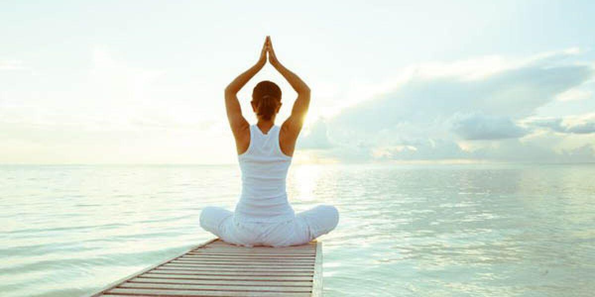Eine Frau sitzt auf einem Steg und macht Yoga