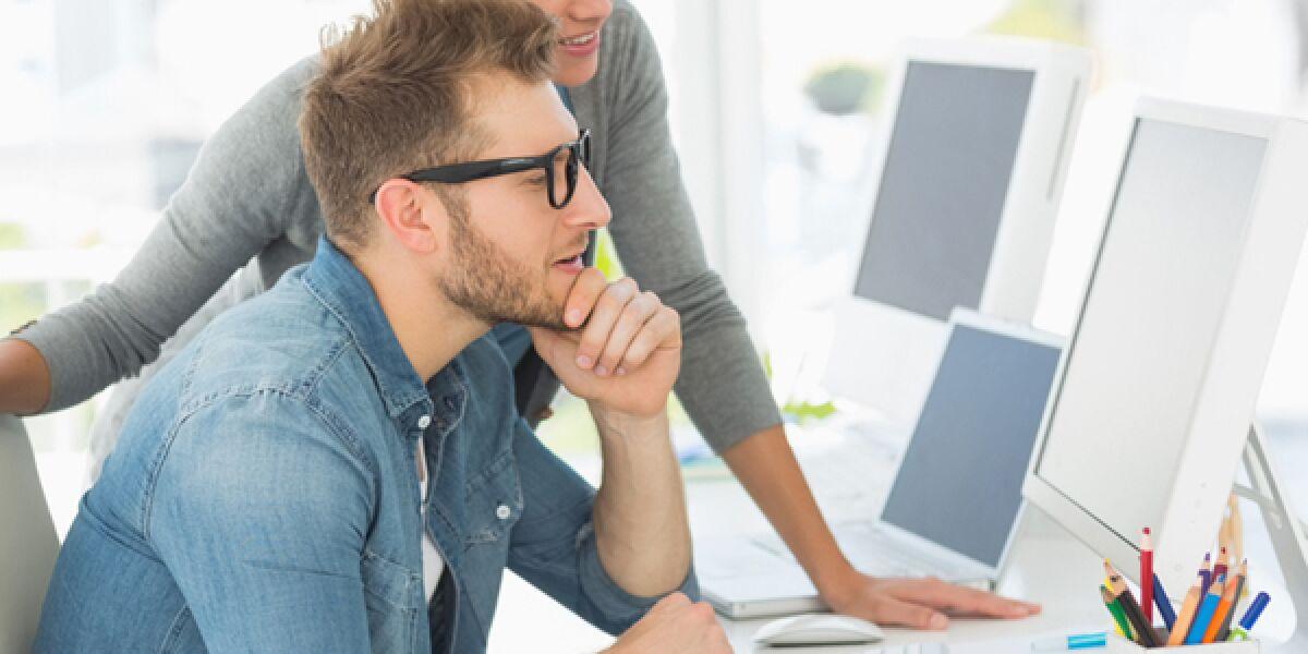 Eine Frau und ein Mann blicken im Büro auf einen Computerbildschirm