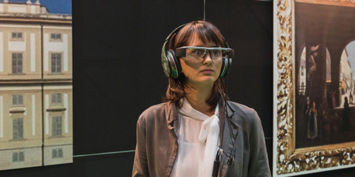 Frau betrachtet durch Brille ein Bild