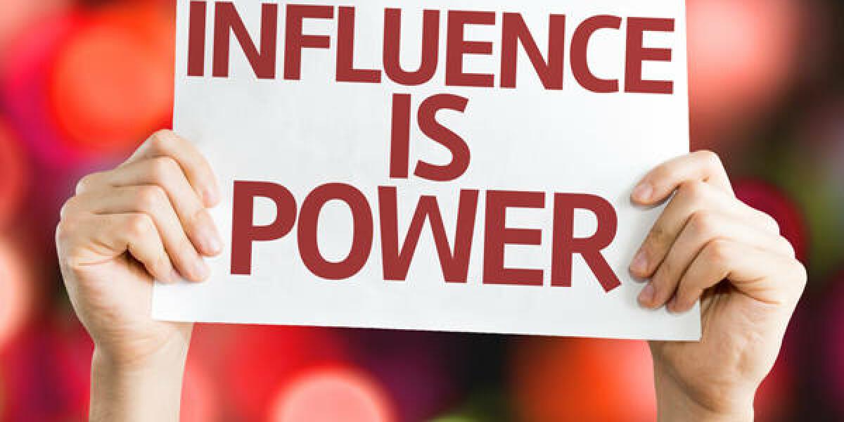 Zwei Hände halten ein Schild mit der Aufschrift: Influence is power