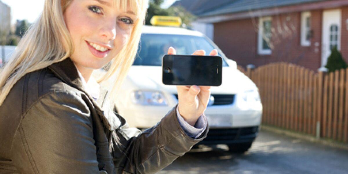Frau hält ein Smartphone in der Hand und sitz vor einem Auto