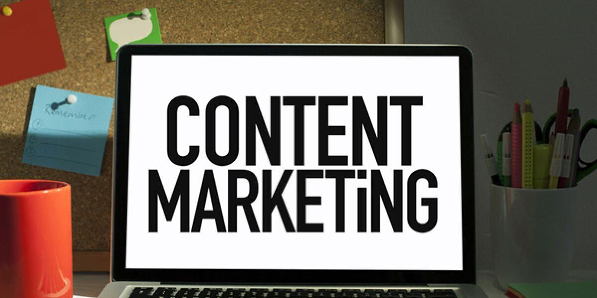 Laptop steht auf einem Schreibtisch und hat die Aufschrift: Content Marketing