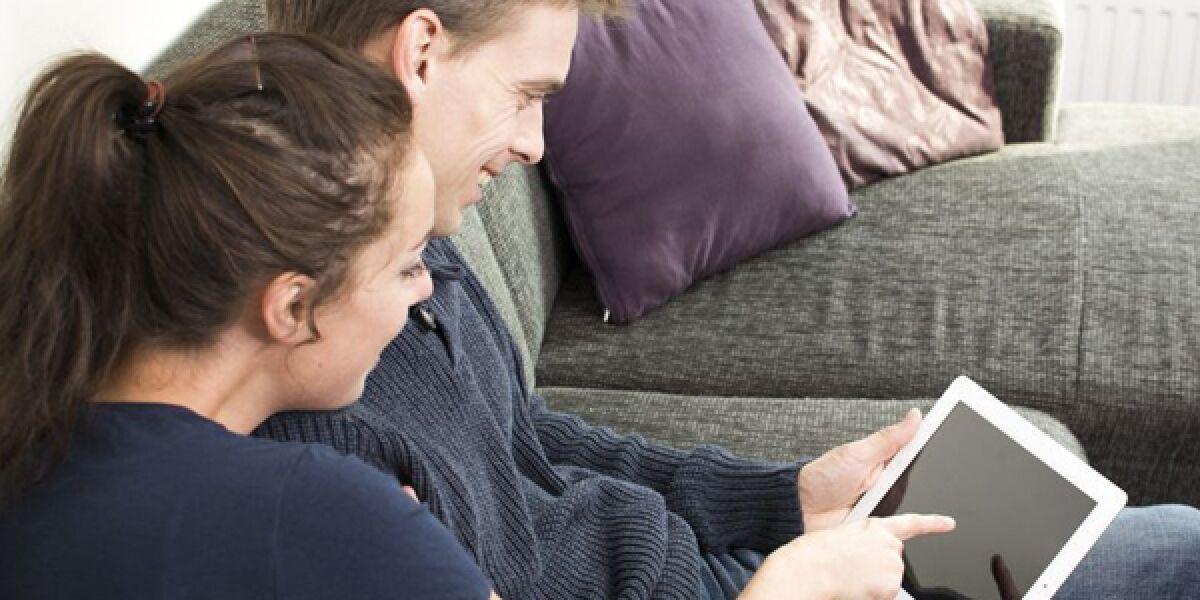 Zwei Menschen mit Tabelt auf dem Sofa
