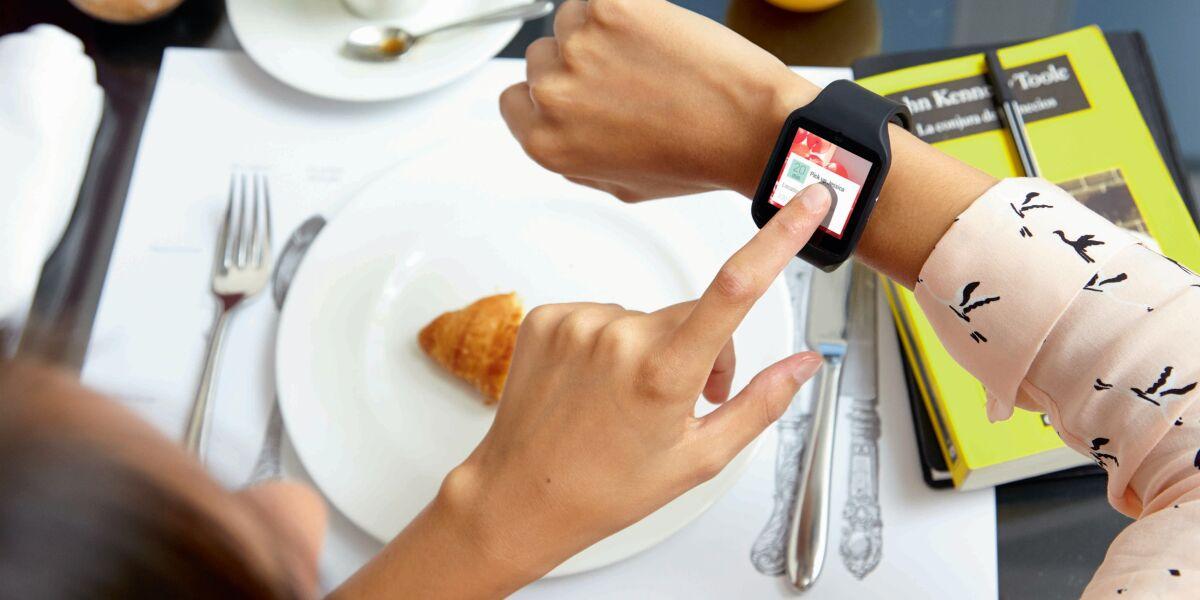 Person tippt auf eine schwarze Sony Smartwatch