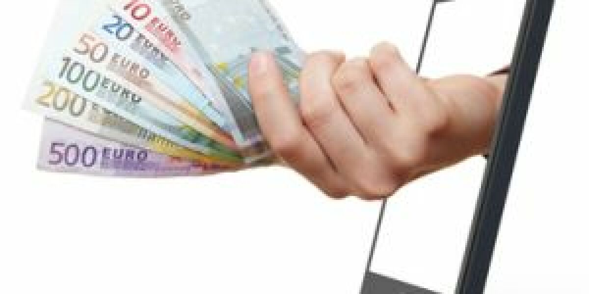 Eine Hand reicht Geldscheine aus dem Smartphone