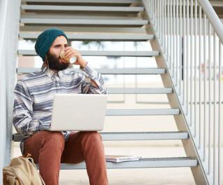 Hipster sitzt mit Laptop und Kaffe auf einer Treppe