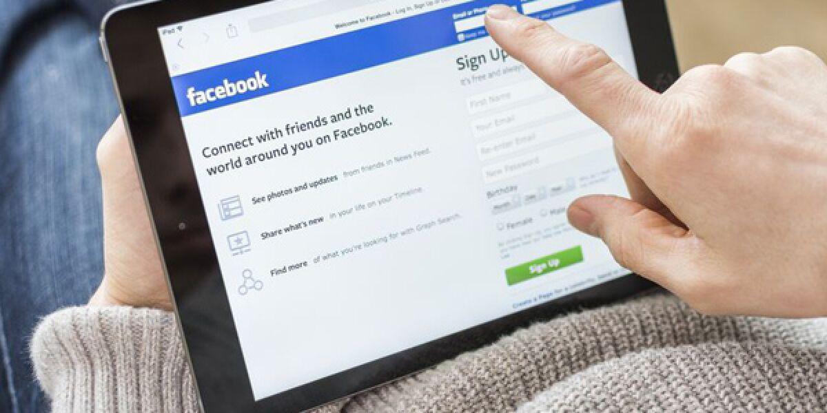 Person surft auf Facebook mit Tablet