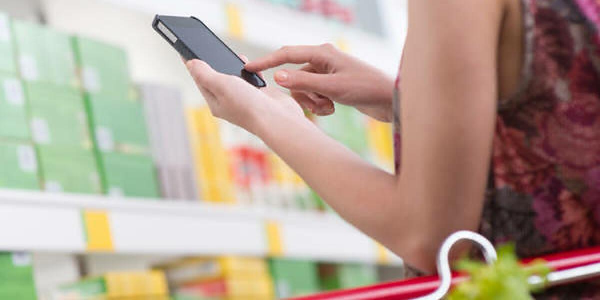 Frau im Supermarkt schaut auf Smartphone