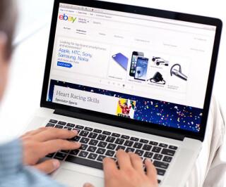 Mann surft auf eBay am PC