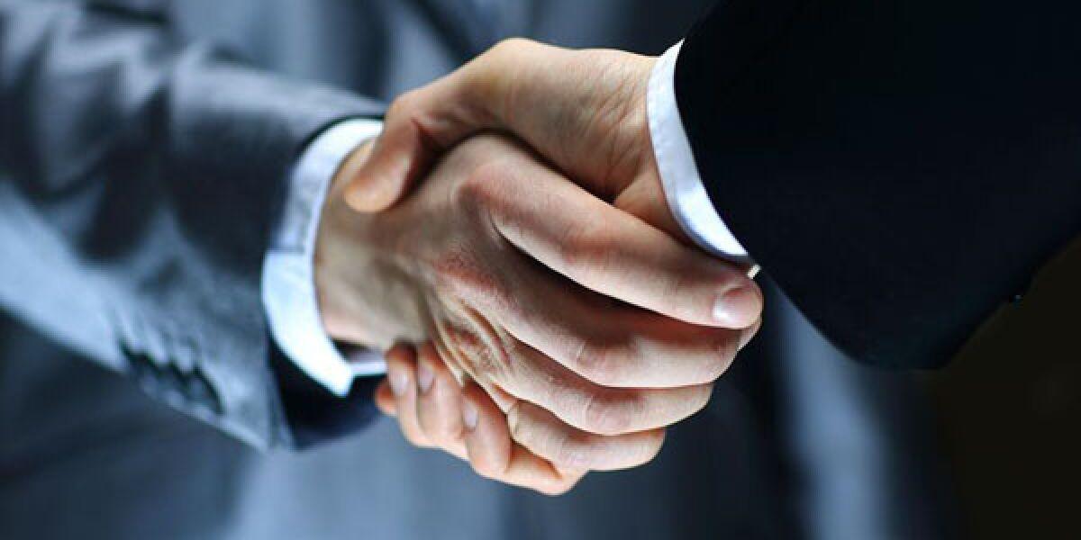 Zwei Männer im Anzug schütteln sich die Hände