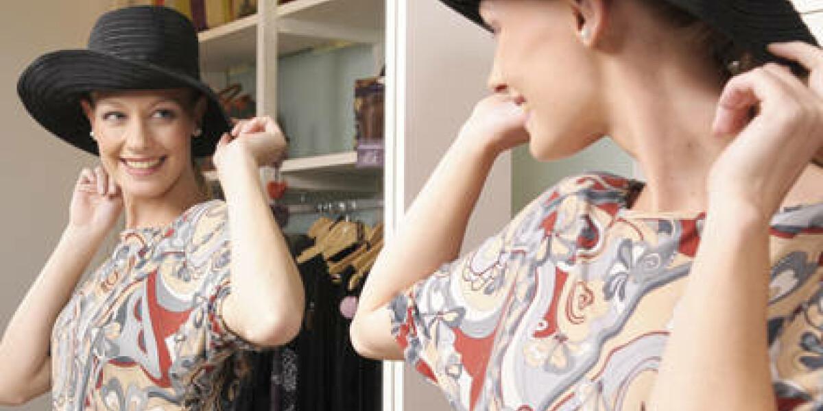 Frau probiert Hut vor Spiegel an