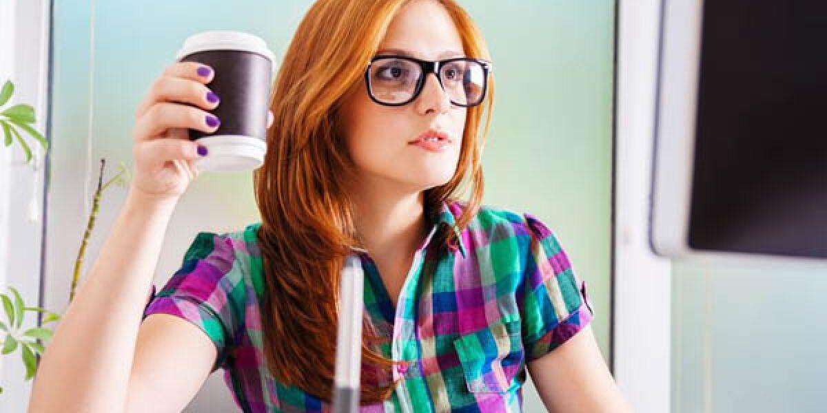 Frau sitzt mit Kaffee in der Hand am Desktop-PC