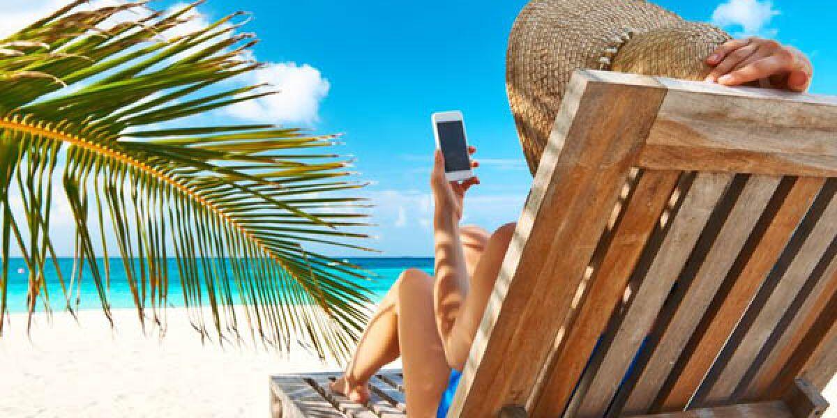Smartphone-Nutzerin am Strand