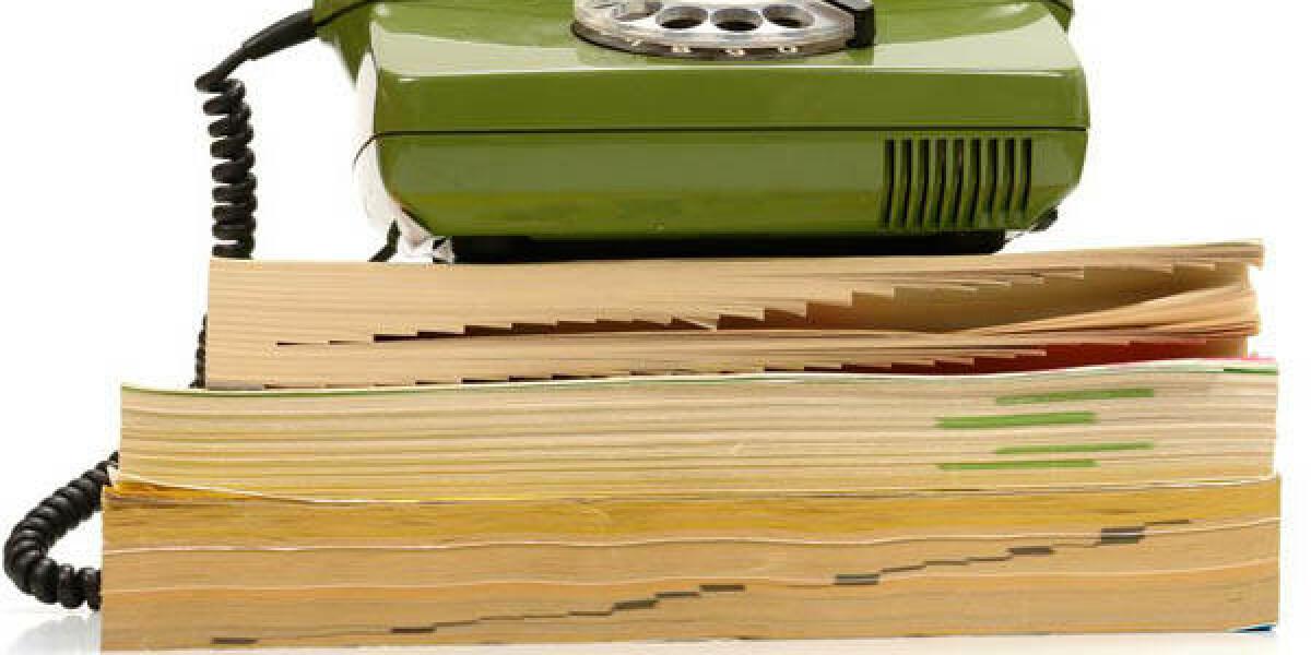 Grünes Telefon mit Wählscheibe auf Telefonbuch