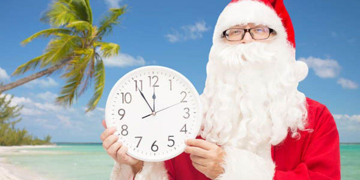 Weihnachtsmann am Strand mit Palme mit weißer Uhr in der Hand