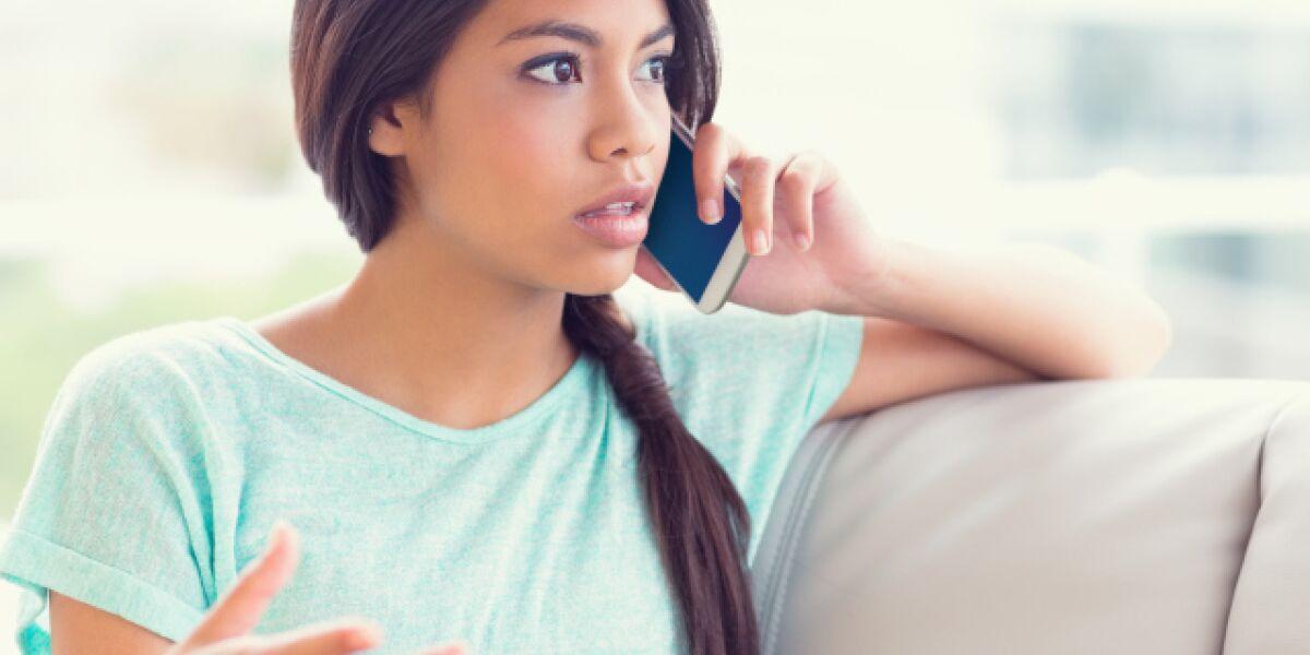 Frau telefoniert auf Couch