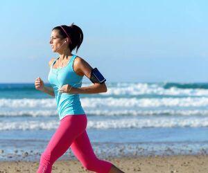 Frau joggt mit Smartphone am Arm