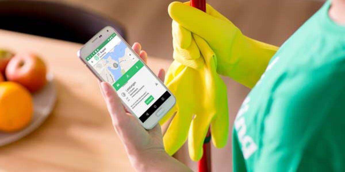 Frau hält Smartphone mit Helpling-App in der Hand