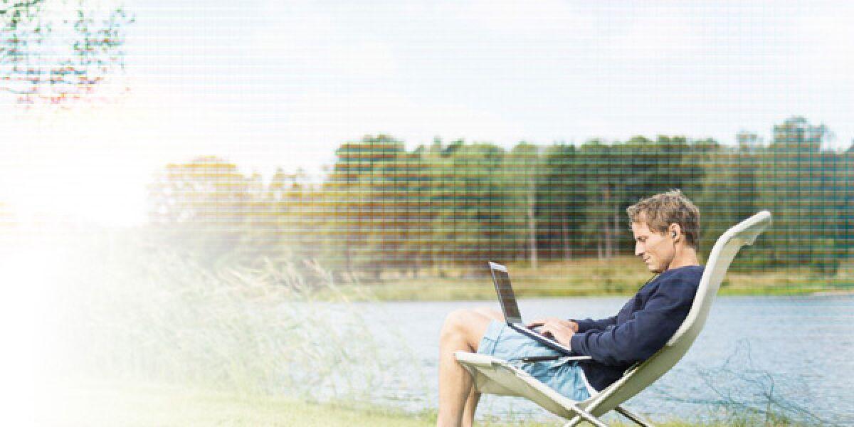 Mann sitzt auf Stuhl im Garten